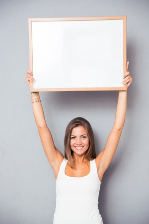 Photo for Smiling young girl holding blank board over gray background. Looking at camera - Royalty Free Image