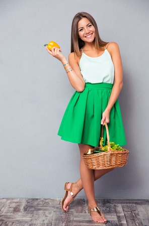 Full length portrait of a smiling attractive woman holding basket with vegetables over gray background