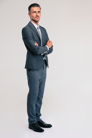 Foto de Full length portrait of a confident businessman standing with arms folded isolated on a white background. looking at camera - Imagen libre de derechos