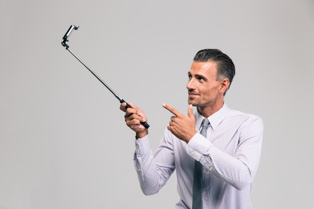Photo for Portrait of a handsome businessman holding selfie stick isolated on a white background - Royalty Free Image