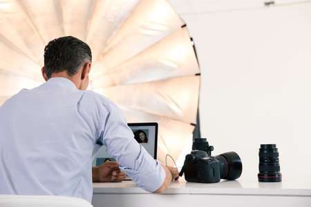 Photo for Back view portrait of photographer using laptop at his workplace - Royalty Free Image