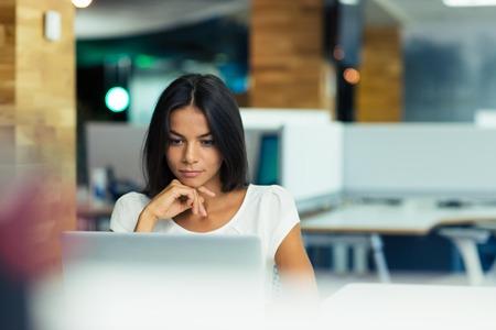 Foto de Portrait of a serious businesswoman using laptop in office - Imagen libre de derechos