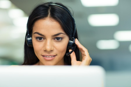 Photo pour Happy businesswoman working on laptop with headphones in office - image libre de droit