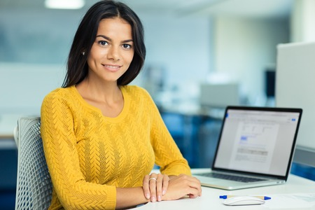 Foto de Portrait of a happy casual businesswoman in sweater sitting at her workplace in office - Imagen libre de derechos