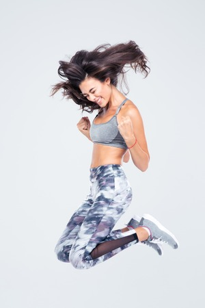 Foto de Full length portrait of a cheerful fitness woman jumping isolated on a white background - Imagen libre de derechos