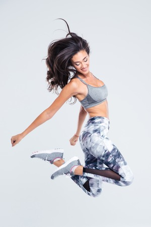 Full length portrait of smiling sports woman jumping isolated on a white background