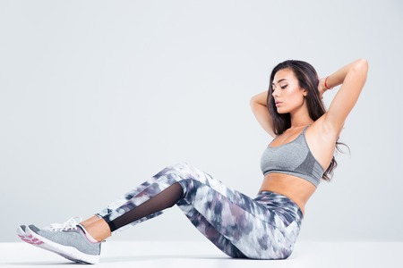 Foto de Portrait of a fitness woman doing abs exercises isolated on a white background - Imagen libre de derechos