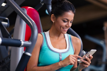 Foto de Portrait of a happy fitness woman using smartphone in gym - Imagen libre de derechos