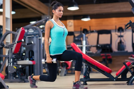 Photo pour Full length portrait of a young woman workout with dumbbells in fitness gym - image libre de droit