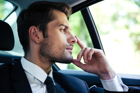 Photo for Thoughtful businessman riding in car - Royalty Free Image