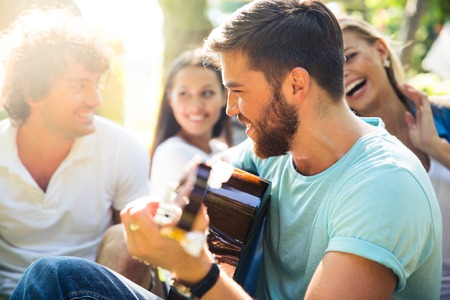 Photo for Group of happy friends with guitar having fun outdoor - Royalty Free Image