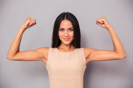 Photo pour Portrait of a happy elegant woman showing her biceps on gray background - image libre de droit