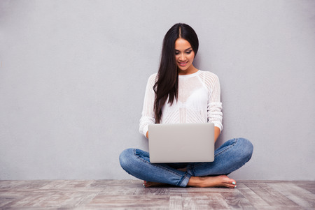 Photo for Portrait of a happy casual woman sitting on the floor with laptop on gray background - Royalty Free Image