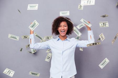 Foto de Concept photo of a cheerful afro american woman standing under rain with money on gray background - Imagen libre de derechos