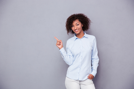 Photo pour Portrait of a smiling afro american businesswoman pointing finger away over gray background and looking at camera - image libre de droit