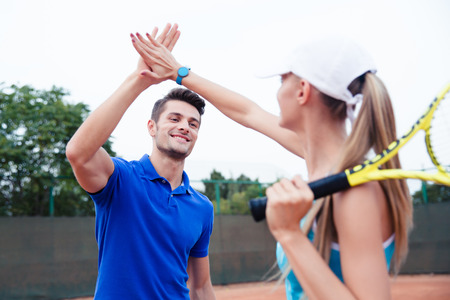 Foto de Male and female tennis players gives five at the tennis court after a match - Imagen libre de derechos