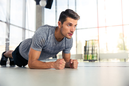 Foto de Portrait of a fitness man doing planking exercise in gym - Imagen libre de derechos