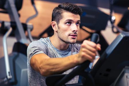Foto de Portrait of a handsome man workout on a fitness machine at gym - Imagen libre de derechos