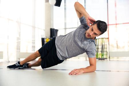 Photo pour Portrait of a handsome man doing side plank at gym - image libre de droit