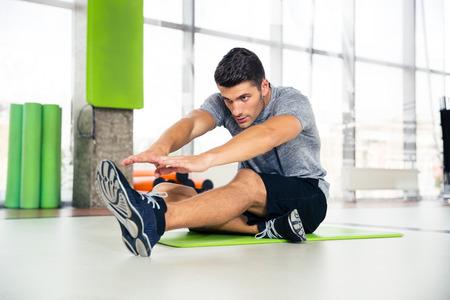 Photo pour Portrait of a fitness man doing stretching exercises at gym - image libre de droit