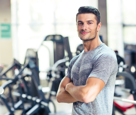 Foto de Portrait of a happy fitness man standing with arms folded at gym and looking at camera - Imagen libre de derechos