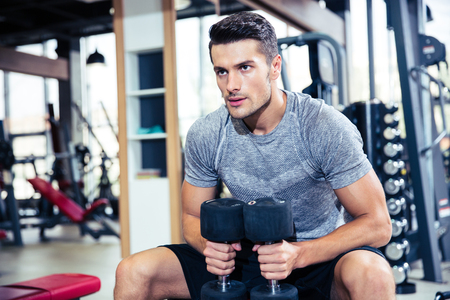 Photo for Portrait of a handsome fitness man workout with dumbbells in gym - Royalty Free Image