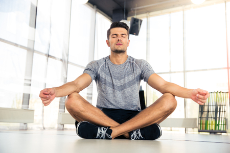Photo for Portrait of a handsome man meditating in fitness gym - Royalty Free Image