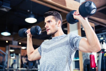 Photo for Portrait of a fitness man workout with dumbbells at gym - Royalty Free Image