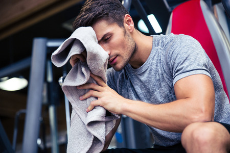 Photo pour Portrait of a handsome man sitting on the bench with towel in fitness gym - image libre de droit