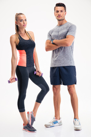 Photo for Portrait of a fitness couple standing isolated on a white background - Royalty Free Image