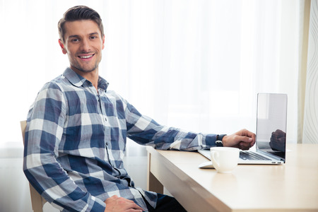 Photo for Portrait of a happy man sitting at the table with laptop and looking at camera - Royalty Free Image