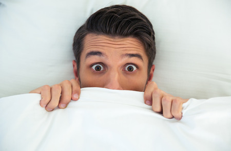 Foto de Man hiding in bed under the blanket at home - Imagen libre de derechos