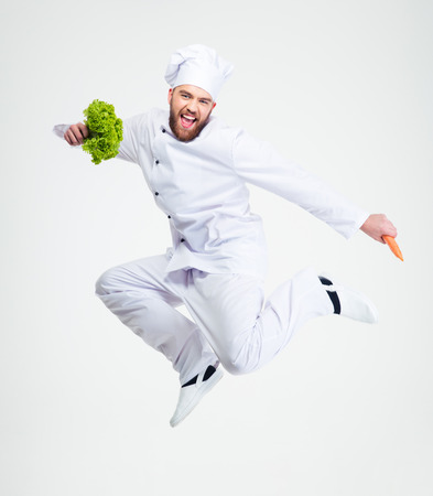 Foto de Full length portrait of a cheerful chef cook dancing isolated on a white background - Imagen libre de derechos