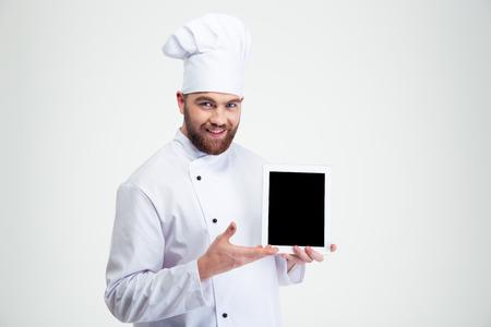 Foto de Portrait of a happy male chef cook showing blank tablet computer screen isolated on a white background - Imagen libre de derechos