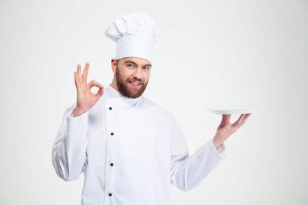 Foto de Portrait of a man chef showing ok sign and empty plate isolated on a white background - Imagen libre de derechos