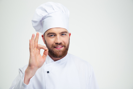 Foto per Portrait of a smiling male chef cook showing ok sign isolated on a white background - Immagine Royalty Free