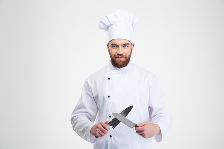Foto de Portrait of a happy male chef cook sharpening knife isolated on a white background - Imagen libre de derechos