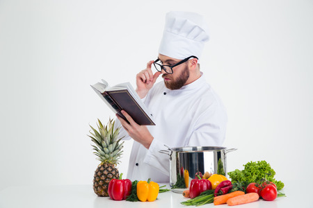 Photo for Portrait of a male chef cook in glasses reading recipe book isolated on a white background - Royalty Free Image