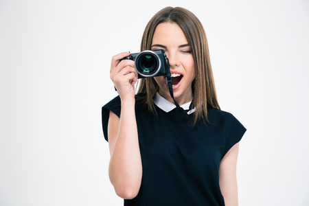 Foto de Portrait of a cheerful woman making photo on camera isolated on a white background - Imagen libre de derechos