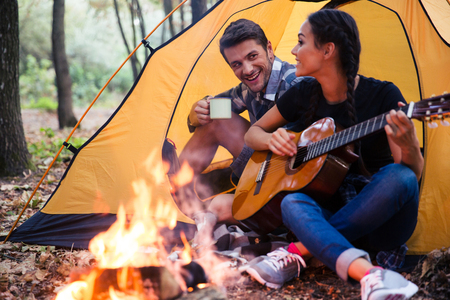 Portrait of a young couple sitting with guitar near bonfire in the forest