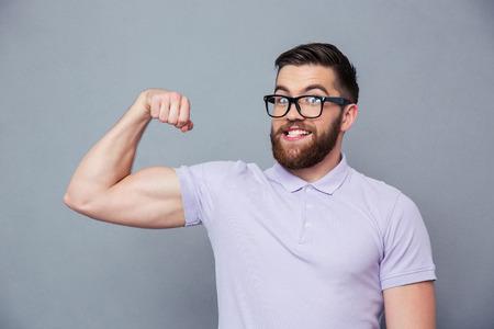 Foto de Portrait of a funny man in glasses showing his muscles over gray background - Imagen libre de derechos