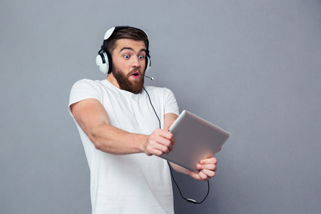 Foto de Portrait of a young man playing on the tablet computer with headphones over gray background - Imagen libre de derechos