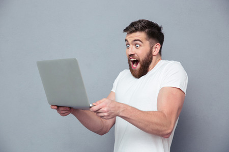 Photo for Portrait of a cheerful man using laptop computer over gray background - Royalty Free Image