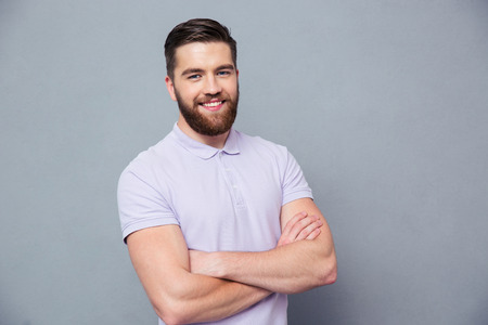 Photo for Portrait of a happy casual man standing with arms folded over gray bakground and looking at camera - Royalty Free Image