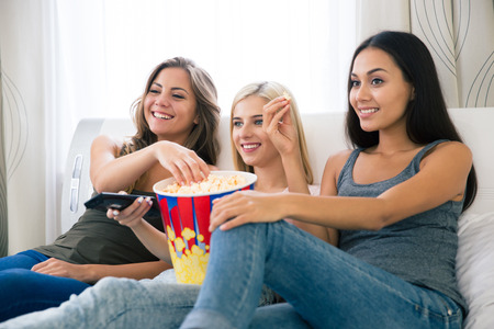Foto de Portrait of a three happy girlfriends eating popcorn and watching tv at home - Imagen libre de derechos