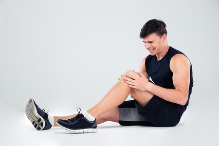 Foto de Portrait of a fitness man suffering from pain in a knee isolated on a white background - Imagen libre de derechos