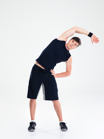 Foto de Full length portrait of a fitness man doing stretching exercises isolated on a white background - Imagen libre de derechos
