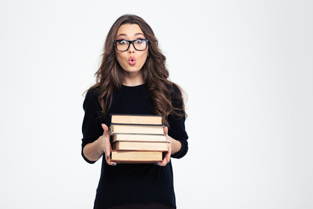 Photo pour Portrait of amazed woman in glasses holding books and looking at camera isolated on a white background - image libre de droit