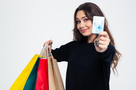 Foto de Portrait of a happy young woman holding shopping bags and bank card isolated on a white background - Imagen libre de derechos