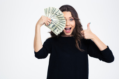 Photo pour Portrait of a cheerful girl covering her eye with dollar bills and showing thumb up isolated on a white background - image libre de droit